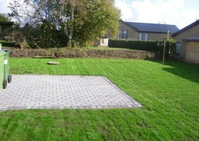 Lille enkel terrasse med fliser og og ny græsplæne