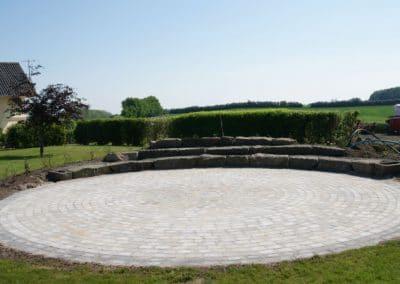 Stor cirkel terrasse med granitsten og beplantning på bagsiden