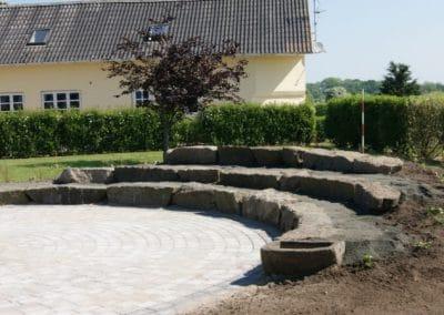 Stor rund terrasse med store granitsten som siddesten